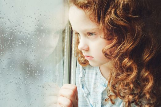 41776833 - sad child looking out the window. toning photo.